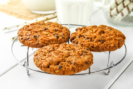 Homemade oatmeal cookies. Cookies on an iron grate on a wooden white table