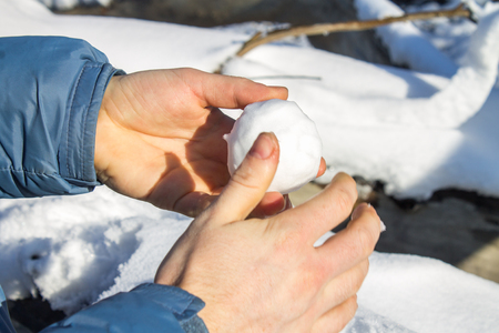Male hands sculpting from the snow small snowballs that would make a snowman