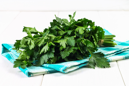 A bunch of green parsley on a white wooden table
