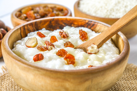 Rice milk porridge with nuts and raisins in wooden bowls on a white wooden table Foto de archivo