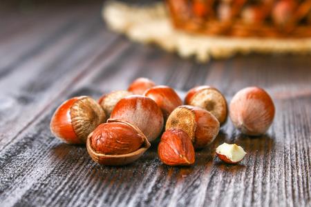 Walnut hazelnuts in a wicker basket on a brown wooden table Stock Photo
