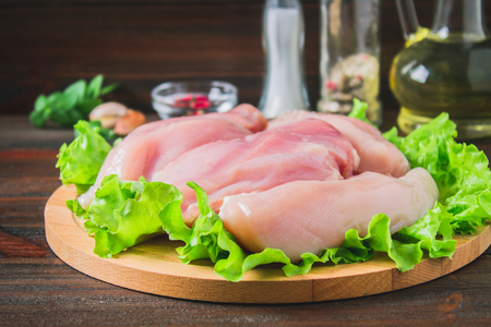 Raw chicken fillet and green salad on a round cutting board on a wooden table background. Meat ingredients for cooking