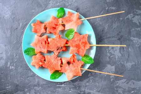 Watermelon in the form of stars on skewers with leaves of mint lies on a plate. The blue dish is like a rocket in space. Top view