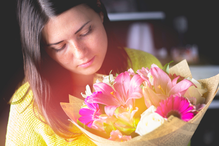 Beautiful girl with dark hair with a bouquet of flowers from a lily, gerbera, white roses and alstroemeria on a dark background. A holiday, a gift