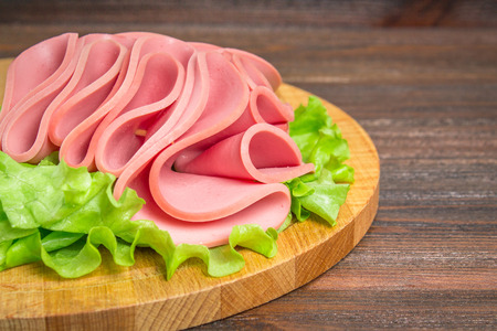 Sliced sausages with salad leaves on the wood background Stock Photo - 92679629
