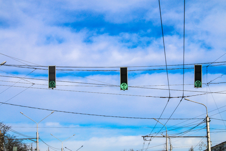 Three green traffic lights hang over the road against the blue sky. Allow signal