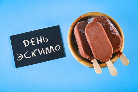 Ice cream eskimo pie on a stick with the text in Russian - Day eskimo pie Stock Photo