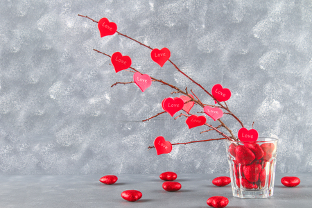Red hearts with an inscription Love hang on branches on a gray concrete background. Love tree. The concept of Valentines Day. A symbol of love