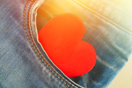 Heart - a symbol of love peeps out of the pocket of jeans trousers. The concept of the day of lovers. St. Valentines Day