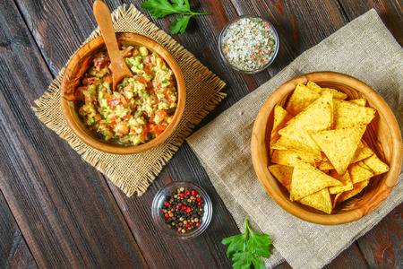 Guacomole is a traditional Mexican sauce consisting of grated avocado, lime juice, red onion, tomatoes, garlic and chili. Served with nachos chips Stockfoto