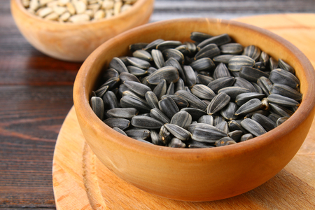 Black peeled and unpeeled sunflower seeds in a wooden bowl on a wooden table
