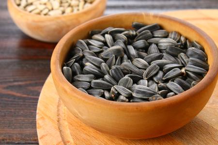 Semi di girasole sbucciati e non sbucciati neri in una ciotola di legno su una tavola di legno