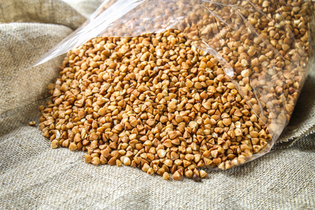 Raw buckwheat is strewed from the package on sacking on a wooden background. Healthy diet food