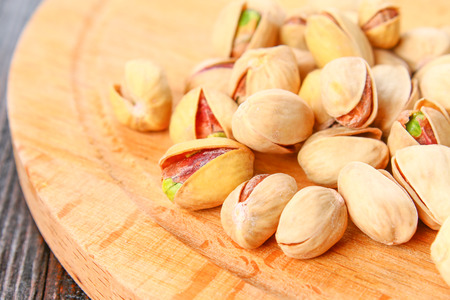 Dish full of pistachios with more pistachios on side