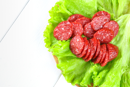 Smoked sausage, salami chopped in slices on a salad on a wooden circular cutting board on a white table