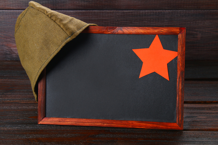 Chalkboard with empty space, military cap and red star on a wooden table. Day of the defender of the fatherland and May 9