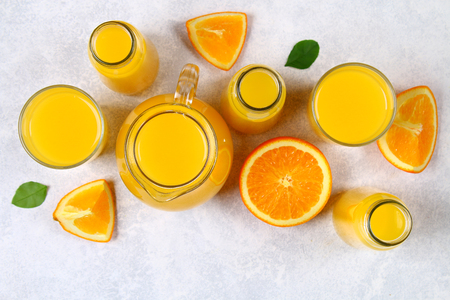 Glass bottles, glasses and a pitcher of fresh orange juice with slices of orange and yellow tubes on a light gray table. Top view. Flat Lay