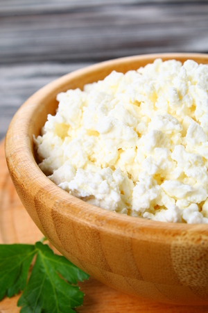 Home cottage cheese in a bowl on a wooden table
