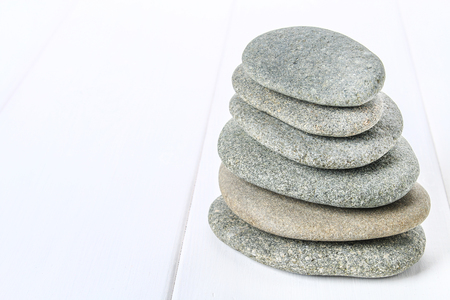 From spa stones make Balances pyramids on white wooden background