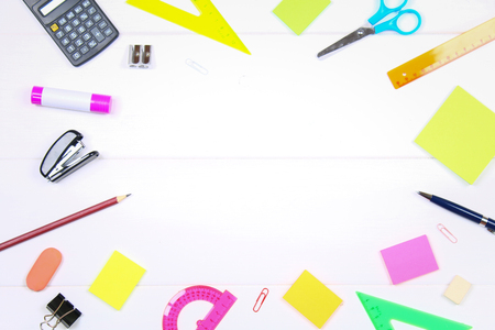 Empty space surrounded by stationery on a white wooden table. Copy the space