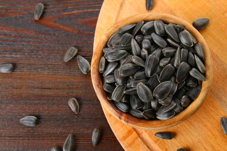 Black unrefined sunflower seeds in a wooden bowl on a wooden table