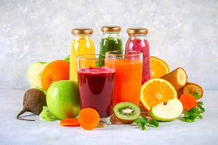 Green, yellow, purple smoothies in currant bottles, parsley, apple, kiwi, orange on a gray table. Orange and purple smoothies in glasses of beet and carrots