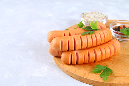 Fried chopped sausages on a wooden board on a gray concrete table Stock Photo