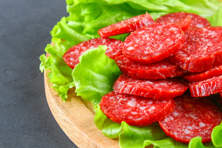Smoked sausage, salami chopped in slices on a salad on a wooden circular cutting board on a concrete gray table Stock Photo