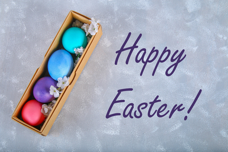 Colored Easter eggs in a gift box on a gray concrete background Standard-Bild