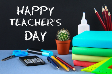 Text chalk on a chalkboard: Happy Teachers Day. School supplies, office, books, apple