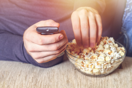 A man with a bowl of popcorn and a remote control in his hand looks at the TV on the sofa