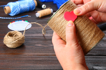 Hands paste the hearts on an iron jar wrapped with string on a wooden table. Handmade