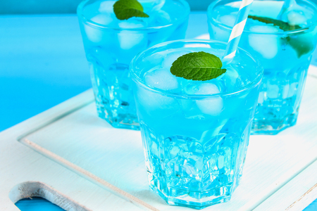Blue cocktail with ice and mint in glasses on a white wooden board on a blue table