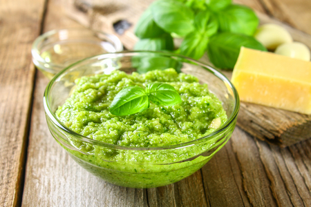 Homemade pesto sauce. Ingredients. Cheese, garlic, basil, pine nuts, olive oil on an old wooden table 免版税图像