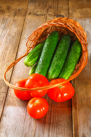 Fresh cucumbers and tomatoes in a basket on an old wooden table Stock Photo
