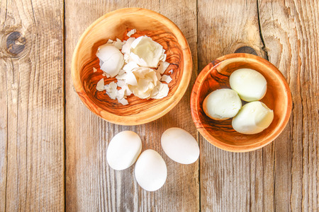 Boiled chicken eggs and their shells in wooden bowls on an old wooden table