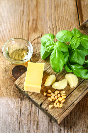 Ingredients for pesto sauce. Cheese, garlic, basil, pine nuts, olive oil Stock Photo