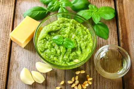 Homemade pesto sauce. Ingredients. Cheese, garlic, basil, pine nuts, olive oil on an old wooden table Stock Photo
