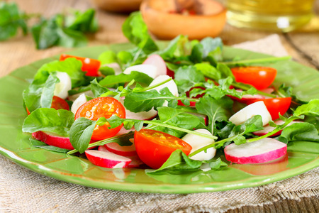 Vegetarian salad of arugula, tomato, radish and mozzarella cheese on an old wooden table