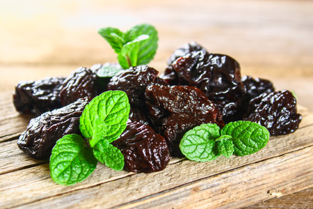 Prunes with mint leaves in a bowl on an old wooden table