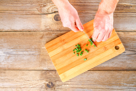Male hands cut a green onion on a cutting board on an old wooden table Stock Photo
