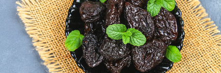 Prunes and fresh mint leaves in a bowl on a concrete table Banque d'images