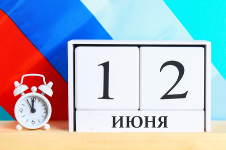 The inscription is June 12, the Day of Russia. Wooden white calendar on the background of the flag of Russia
