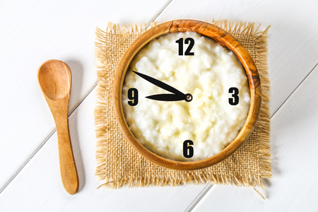 Rice milk porridge with nuts and raisins in wooden bowls on a white wooden table, The concept of a breakfast with a clock.