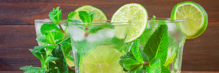 Mojito with mint and lime in a glass and a jug on the round board. Brown wood background 写真素材