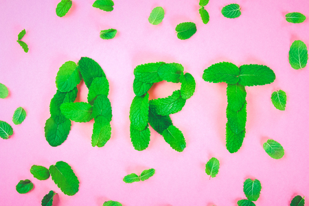 The text of art is laid out of mint leaves on a pink pastel background Stock Photo