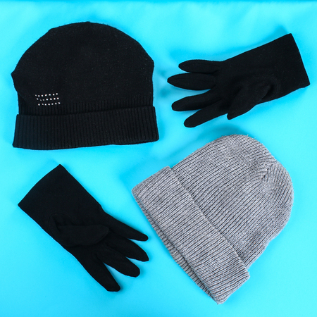 Winter and autumn clothes, hats, scarves, gloves on a blue pastel background
