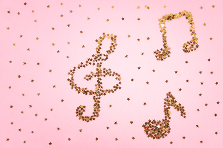 Musical notes of starry golden confetti lying on a pink pastel background 版權商用圖片