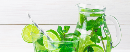 Mojito with mint and lime in a glass and a jug with tubes. White wooden background