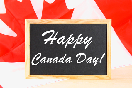 Chalkboard with the word Happy Canada Day on the national flag. Feast of 1 July Stock Photo